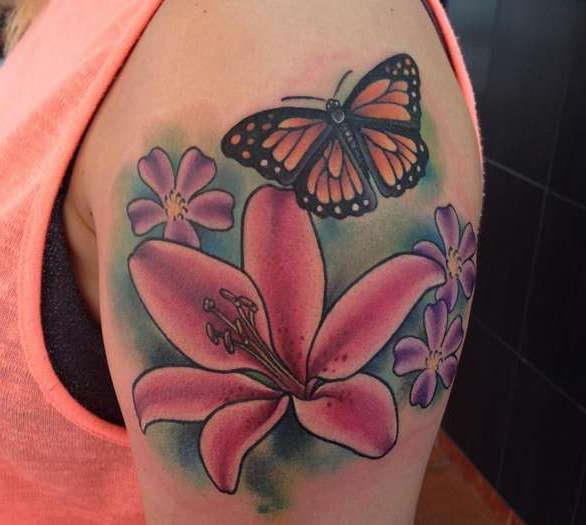 Татуировка лилия с бабочкой на плече девушки