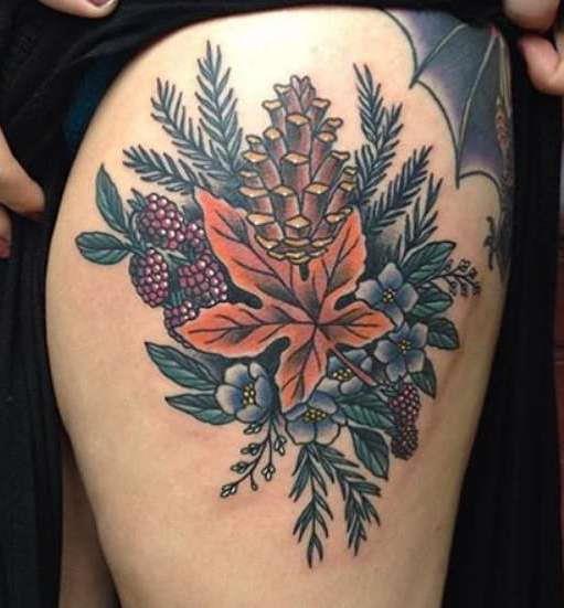 Кленовый лист, шишка и цветы на бедре девушки