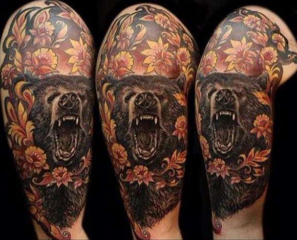 Татуировка оскала медведя с цветами на плече