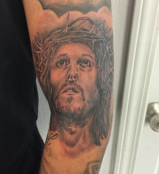 Татуировка Иисуса, который смотрит вверх на плече