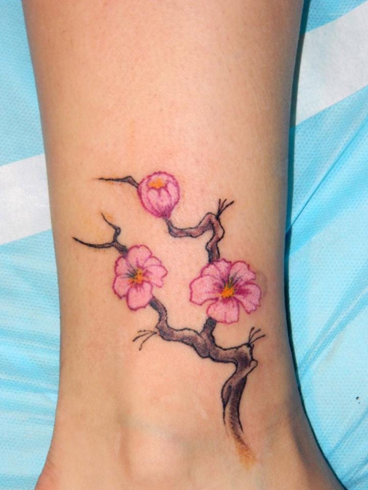 Женская татуировка сакура на лодыжке
