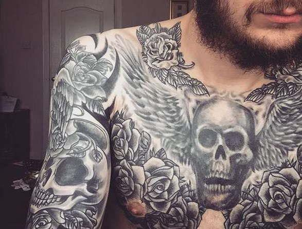 Татуировка на груди в виде черепа, крыльев и цветов