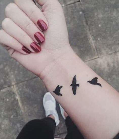 Стая из трех птиц на запястье девушки