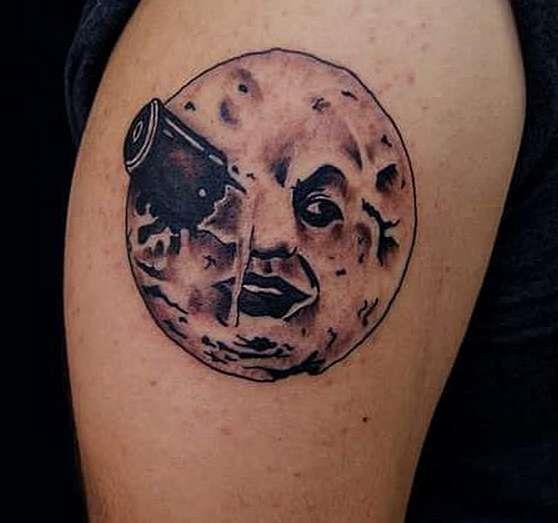 Торчащий предмет из глаза луны: татуировка на плече парня