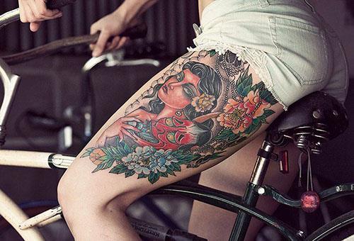 Татуировка у девушки на бедре